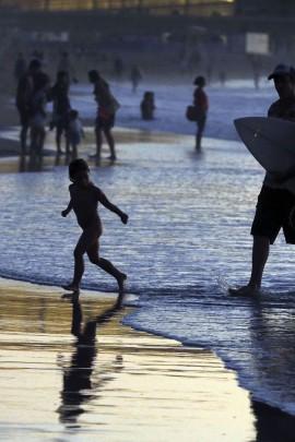 Algunos bañistas disfrutan al atardecer en la playa de la Zurriola de San Sebastián