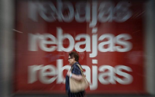 ESPAÑA REBAJAS DE VERANO:GRA038 MADRID, 01/07/2015.- Una mujer pasa delante del escaparate que exhibe un cartel publicitario de un centro comercial en Madrid en el primer día de las rebajas de verano.- EFE/JUAN CARLOS HIDALGO.