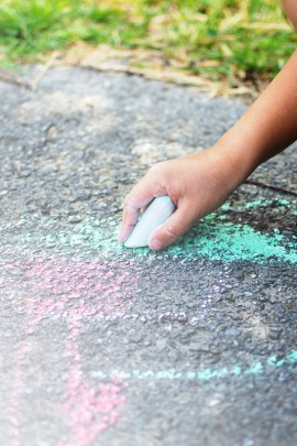 Children drawing in the park with chalks of various colors. Selective focus on hand.